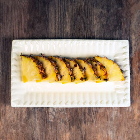 Pineapple fruit cut in wedges on plate wooden background healthy snack