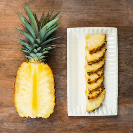 Pineapple fruit cut half and wedges and displayed on white plate and wooden background. Square Composition. Juicy organically grown ripe and sweet Banco de Imagens
