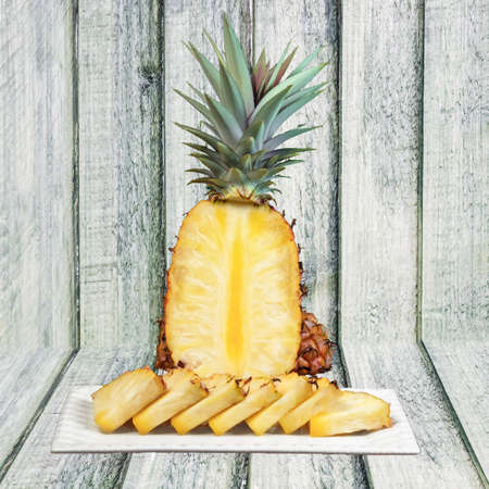 Pineapple cut wedges on the plate wooden background healthy snack