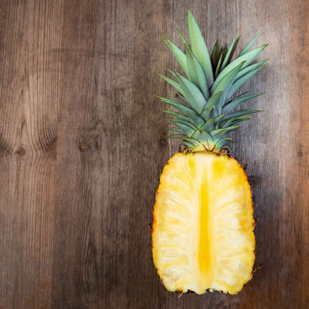 Pineapple fruit cut half on top wooden background negative space. Square Composition. Juicy organically grown ripe and sweet