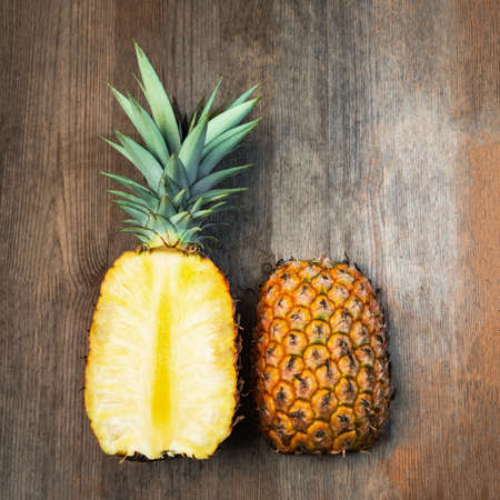 Pineapple fruit cut two halves top wooden background negative space. Square Composition. Juicy organically grown ripe and sweet Banco de Imagens