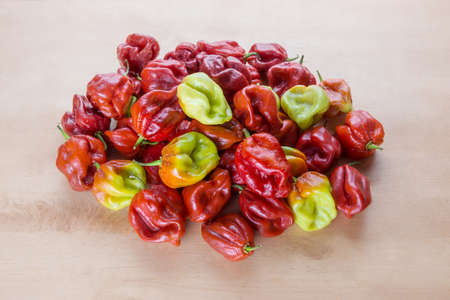 Red Hot Chilli pepper Scotch Bonnet Caribbean Antillais on wooden background colourful Stock Photo