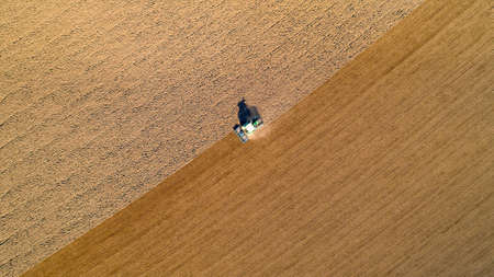 Aerial photo of a tractor ploughing a field in the french countryside