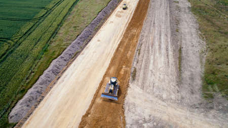 Aerial photo of a backhoe loader and a steamroller on a road work