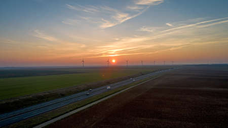 Turbiny wiatrowe wzdłuż autostrady o zachodzie słońca, Francja Zdjęcie Seryjne