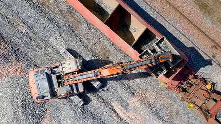 Aerial photo of an excavator loading a wagon with gravel