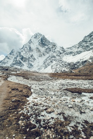 Valley of Himalayan mountain with mountain river on track to Everest base camp. High mountain with snow peaks.