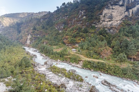 Valley of Himalayan mountain with mountain river on track to Everest base camp. High mountain with snow peaks, Nepal