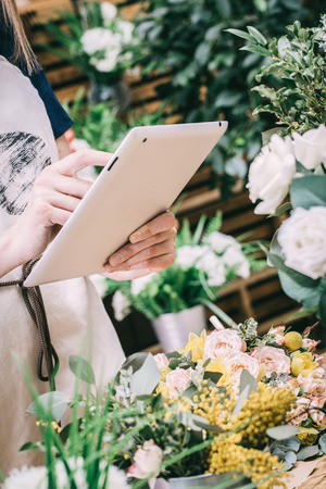Young girl takes pictures of floral bouquets on a tablet Stock Photo