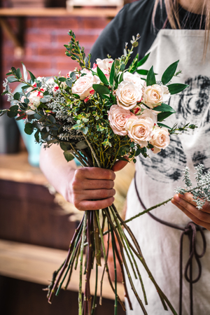 Faceless shot of florist composing fresh blooming flowers together in big bouquet. Stok Fotoğraf