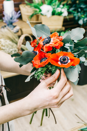 Anonymous saleswoman showing vivid small bouquet with red poppy flowers and green foliage.