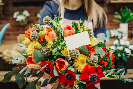 Professional florist showing amazing vivid floral composition with blank white postcard.