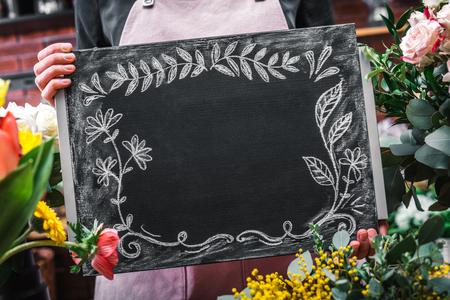 Faceless shot of salesperson showing ornamental blank blackboard in flower market.