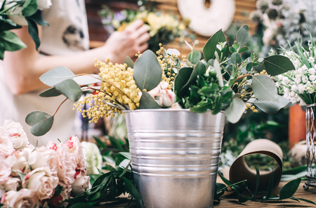 Interior shot of desktop filled with fresh blooming flowers in bucket. Stock Photo