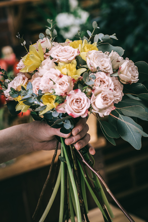 Crop salesperson demonstrating wonderful bunch with roses and green branches.  Stock Photo