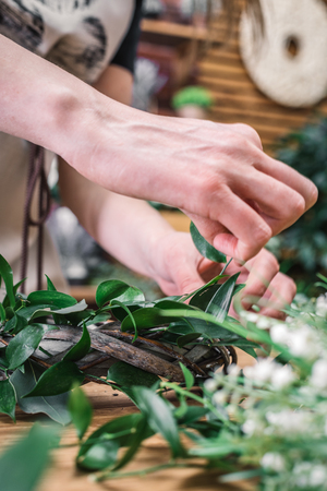 Crop close-up view of professional florist worker making wonderful wreath with fresh leaves. Foto de archivo - 96587659