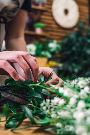 Close-up shot of woman composing tender green branches on wooden wreath making beautiful decor.