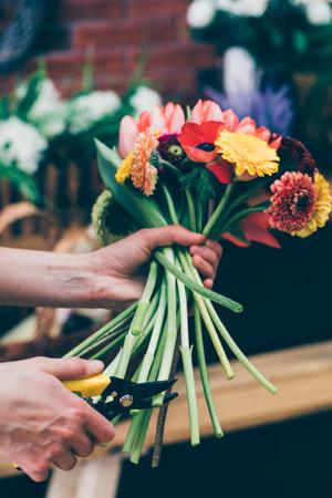 Crop shot of florist cutting ends of flowers stems arranged in vivid bouquet.