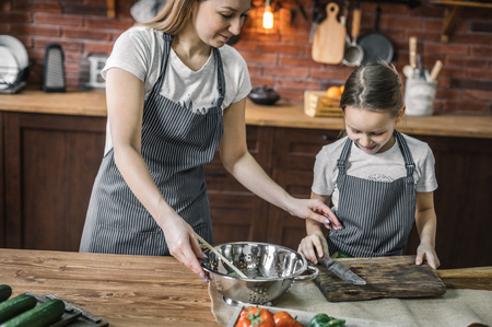 Girl and mother preparing to cook Stock Photo