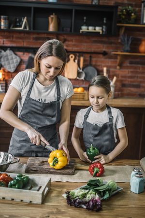Adult woman and girl slicing peppers