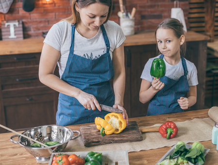 Woman and daughter cutting pepper