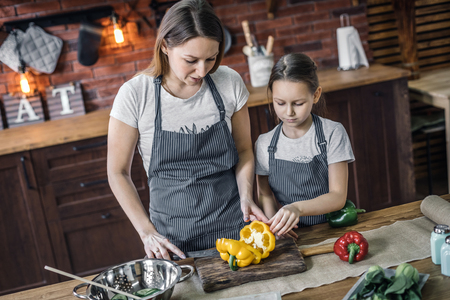 Mother and daughter with peppers on kitchen Stock Photo