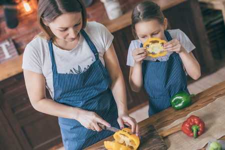 Mother and daughter preparing pepper on kitchen