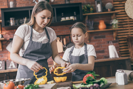 Mother and daughter preparing yellow pepper Stock Photo