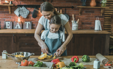 Woman and girl cutting pepper