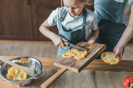 Girl putting cut pepper to bowl Stock Photo
