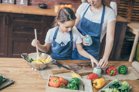 Girl mixing salad with mother