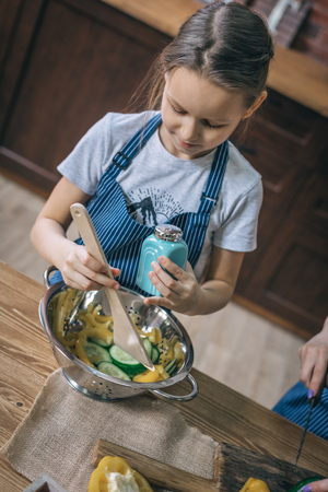 Little girl cooking and seasoning salad