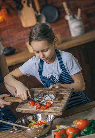 Girl putting tomatoes to bowl