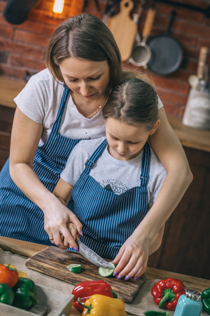 Mother teaching girl to cut the cucumber