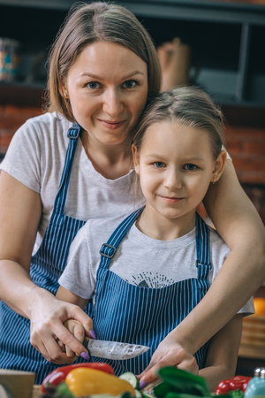 Mother and daughter looking at camera on kitchen Stock Photo