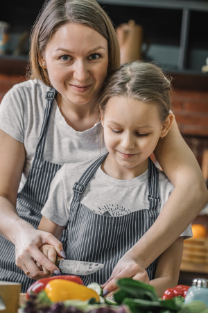 Mother looking at camera and cooking with daughter