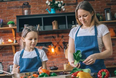 Woman with daughter preparing vegetables