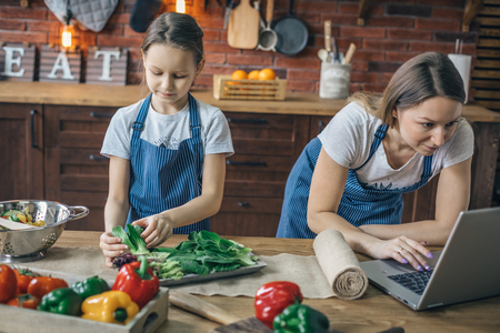Girl preparing ingredients and mother watching laptop Stock Photo