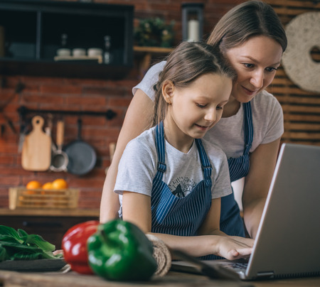 Girl typing on laptop while cooking with mother