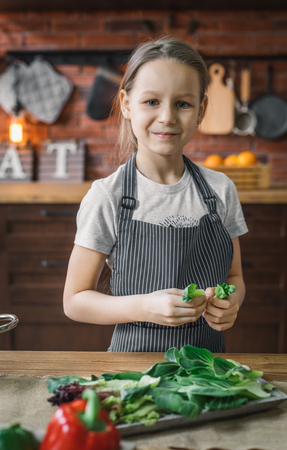 Girl standing with green herb