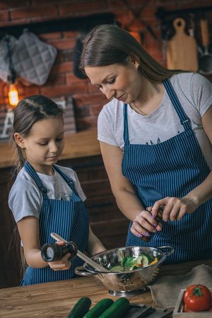 Mother and daughter seasoning healthy salad