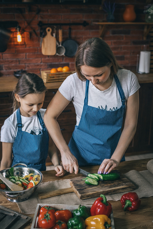 Girl watching mother cooking cucumbers