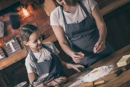 Mother and daughter putting egg to flour Stock Photo