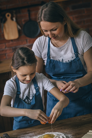 Girl and mother cracking eggs to flour