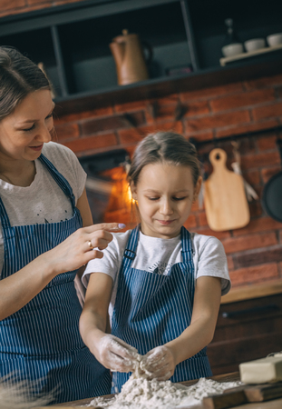 Mother and daughter having fun on kitchen