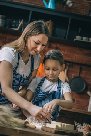 Woman and girl making dough on kitchen Stock Photo