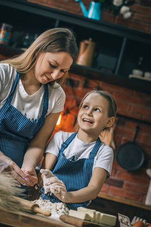Smiling girl helping to mother with dough