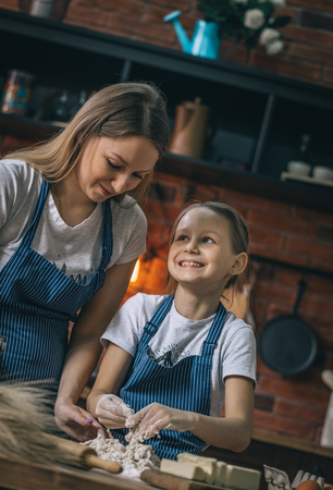 Smiling girl looking at mother while cooking