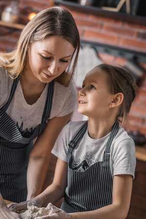 Little girl looking at mother while cooking