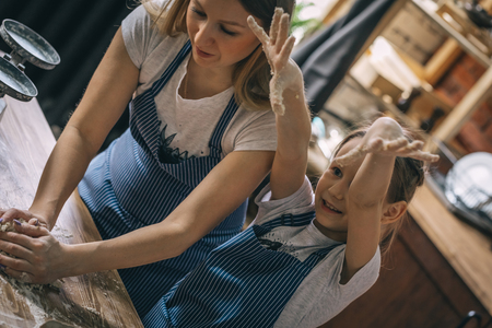 Girl having fun while cooking with mother